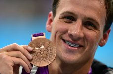 US swimmer Ryan Lochte poses with his bronze medal after the podium ceremony for the men's 200m backstroke swimming event at the London 2012 Olympic Games on August 2, 2012 in London.  AFP PHOTO / MARTIN BUREAU        (Photo credit should read MARTIN BUREAU/AFP/GettyImages)